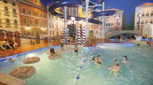 Kids and parents splashing in an indoor pool in a setting made to look like Italy at Venetian Waterpark at Holiday Inn, Maple Grove