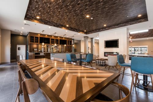 A long wooden table sits in the middle of the common dining area at the Four Points in Elkhart, Indiana