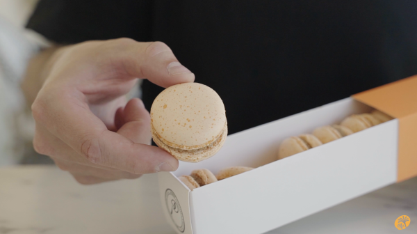 Image a sleeve of pumpkin spice flavored macarons with one pulled out and held towards to the camera for a closer look.