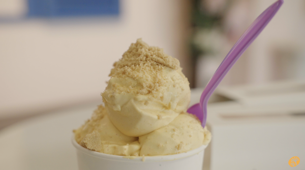Image of a double scoop of pumpkin spice ice cream placed in a white cup with a pink spoon.
