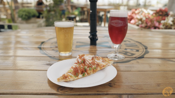 Slice of pizza on a wooden table, positioned in between two beers. One light, caramel colored beer to the left and one purple colored beer to the right.