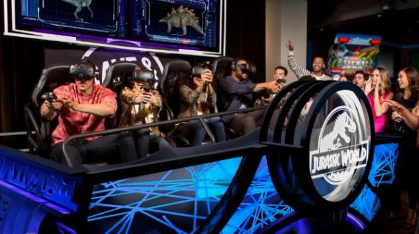 A group of adults wearing virtual reality goggles sitting on a ride with the Jurassic Park logo on the front at Dave & Buster's