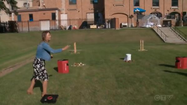 A woman plays a game in a grassy area