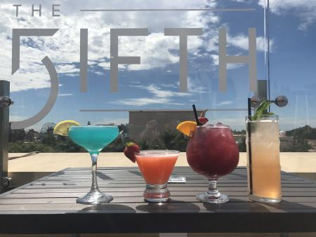 Four cocktails lined up against a sign that reads The FIFTH.