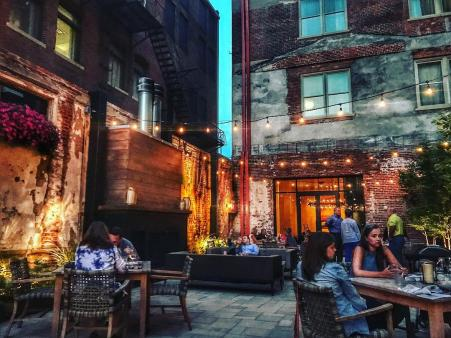 patio area of Coppin's at Hotel Covington restaurant and bar.  mood lighting overhead and people gathered dining and drinking at tables on a patio