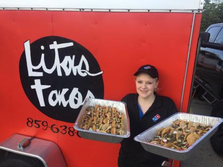 woman holding two trays of tacos in front of lita's taco truck in florence ky