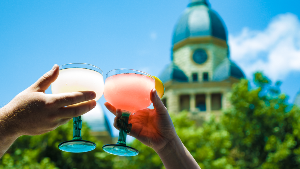 Two people cheers glasses of margaritas with the courthouse in the background