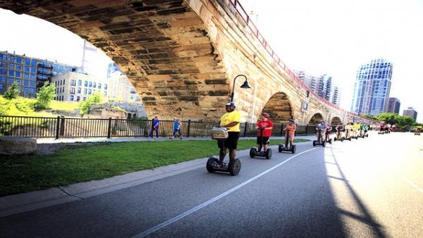 People riding segways under the Stone Arch Bridge