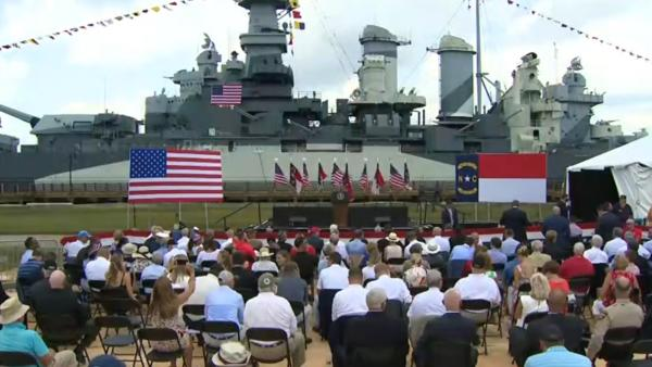 Podium and crowd with flags in front of World War II Monument in Wilmington, NC