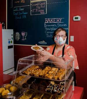 woman in mask serving food