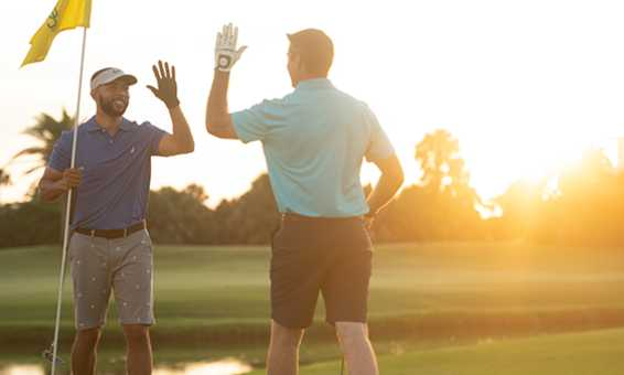 Two golfers high five each other on the green