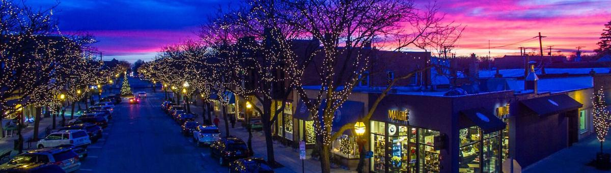 Aerial view of Downtown Glen Ellyn with holiday lights on trees at sunset