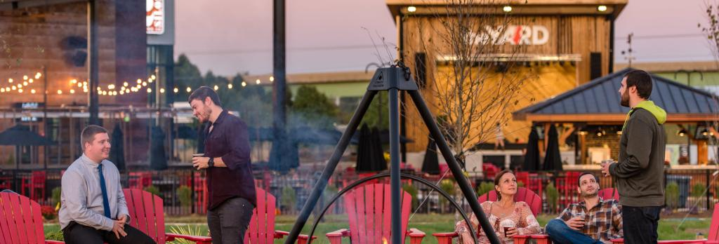People sitting around a fire in red Adirondack chairs ead8d9d9bc9