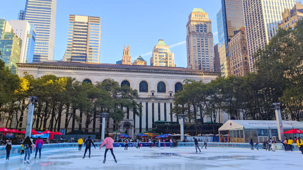 People skating in Bryant Park with Manhattan Sy
