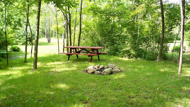 A picnic table and fire pit at Cherry Hill Campground