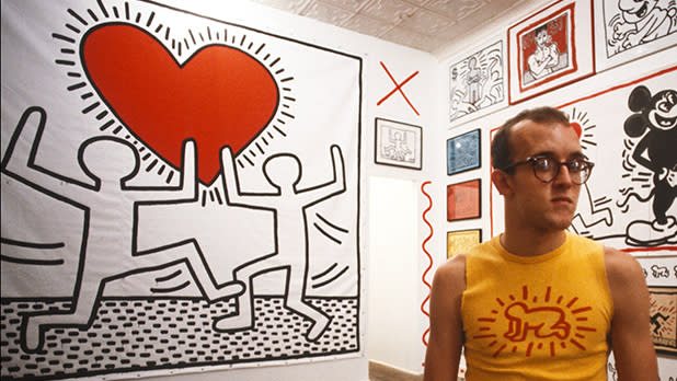 Keith Haring standing in front of his famous heart with two dancing figures work