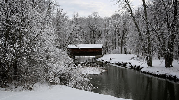 A snowy scene featuring Hyde Hall Covered Bridge in Glimmerglass State Park