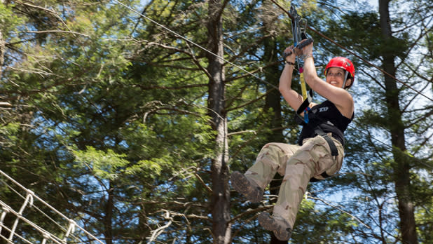 A person soars through the trees on the Hunter Mountain zipline
