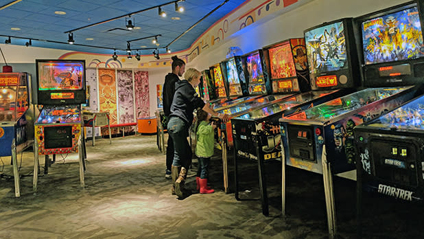 Family playing pinball at Strong National Museum of Play