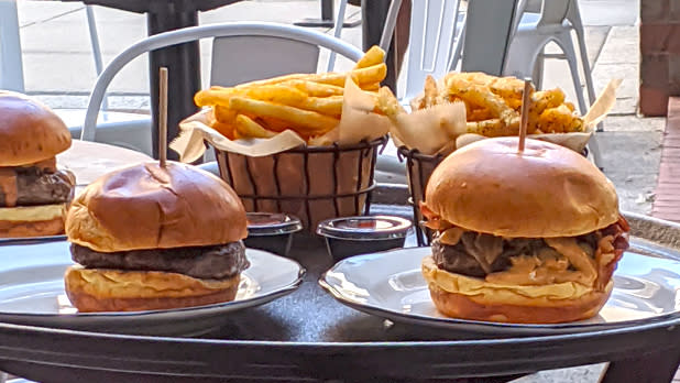 Two burgers with fries on a table at Kings Kobe in NYC