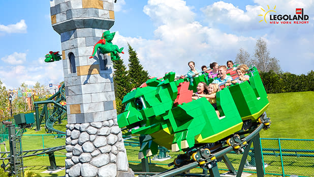 Guests ride a Lego dragon coaster by a tower