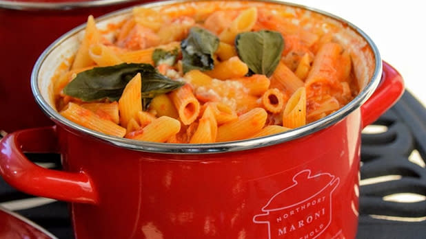 A red pot filled with pasta in red sauce with basil