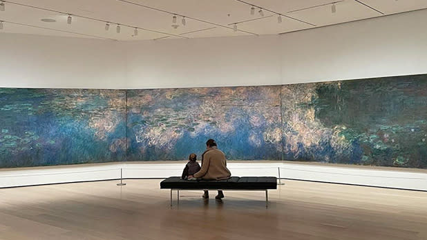 An adult and child sit on a bench in front of artwork at MoMA