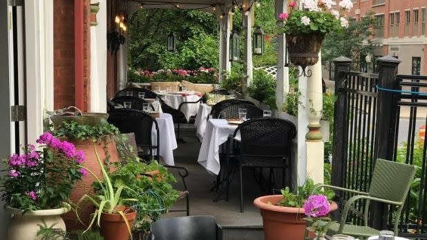 A terrace with restaurant tables, purple flowers and green plants