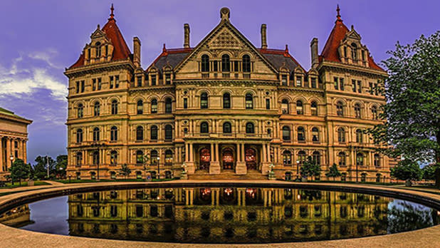 The New York State Capitol with a fountain in front of it reflecting its image