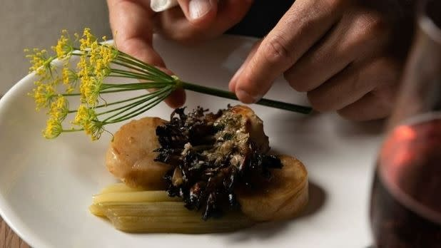 A chef places a flowery herb atop ingredients on a dish at North Fork Table