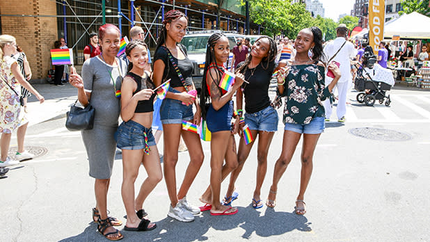 Six Black women and girls holding Pride flags on a city street