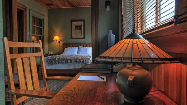 A table and lamp, plus a bed, in a room at Roycroft Inn