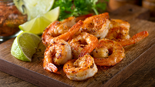 Roasted shrimp and limes on a cutting board