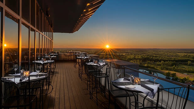 An outdoor dining area on a high floor with a view of sunset