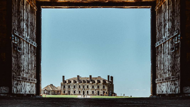 A view of Fort Ontario through a square alley with no clouds in the sky and green grass in the distance