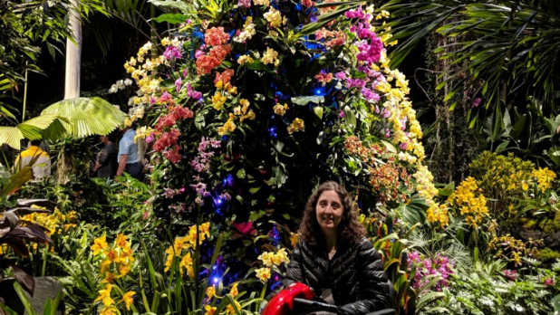 A woman poses in her wheelchair in front of orchids at the orchid show at the New York Botanical Gardens in the Bronx.