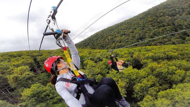 Two people on the Zipline Canopy Tours at Hunter Mountain with red helmets