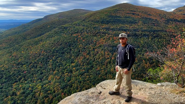 Official I LOVE NY Leaf Peeper Feroz standing in front of a mountain with fall foliage