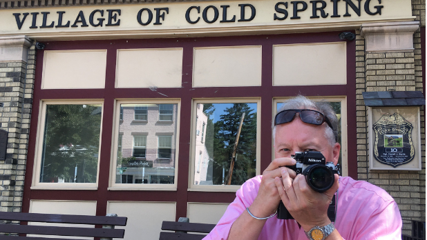 A photo of Official I LOVE NY Leaf Peeper Bill with his camera outside in Village of Cold Spring