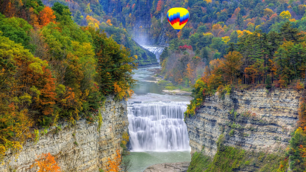 A rainbow balloon flying over Letchworth Falls with fall foliage all around