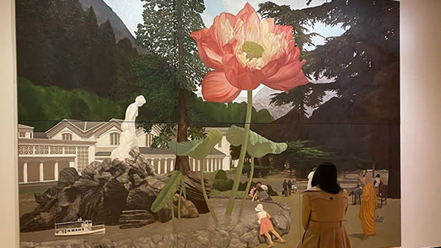 A person stands before a painting of a flower and buildings