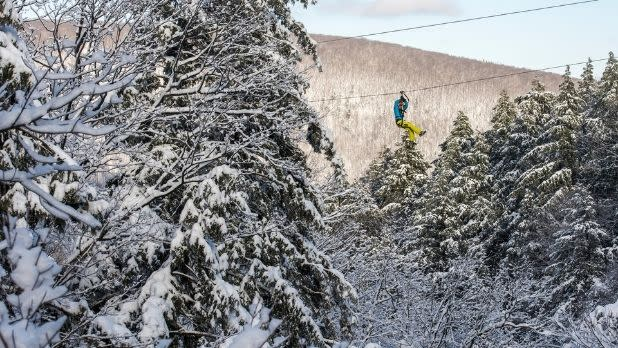 A person ziplines among snow-covered trees