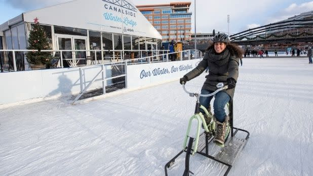 A woman rides an ice bike at Canalside