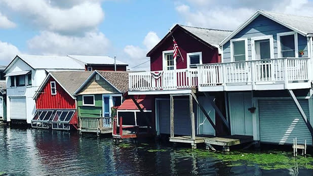 white, red, green and light blue boathouses on a lake