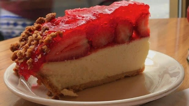 A slice of cheesecake with strawberries on top