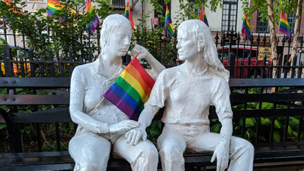 Statues of two people in Christopher Park holding a rainbow flag