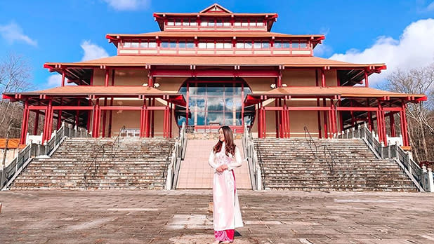 A woman in a white dress poses in front of the Chueng Yen Monastery