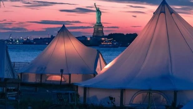 Glamping tents on Governors Island with a view of the Statue of Liberty at sunset