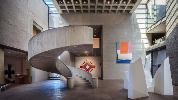 A spiral staircase and art inside the Everson Museum