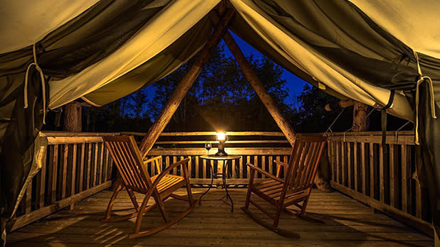 A glamping tent at night with a candle illuminating two rocking chairs